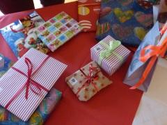 Bunt eingepackte Geschenke auf einem Tisch mit roter Tischdecke.