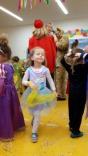 Kleines Mädchen als Prinzessin verkleidet tanzt durch die Turnhalle.