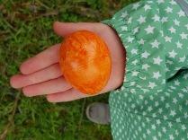 Kinderhand hält ein leuchtend buntes Ei